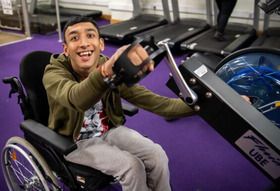 Young man in wheelchair enjoying gym workout